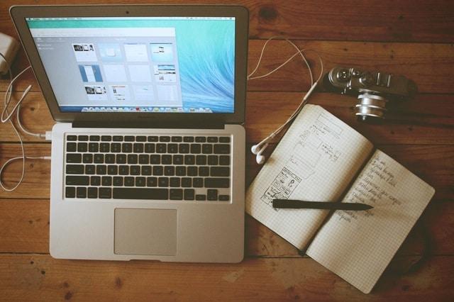 Image d'un ordinateur, un cahier et un appareil photo. Cette image symbolise une séance de travail.